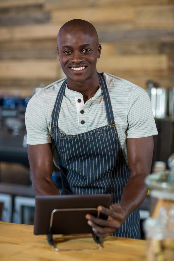 Kelner używa cyfrową pastylkę przy kontuarem fotografia royalty free