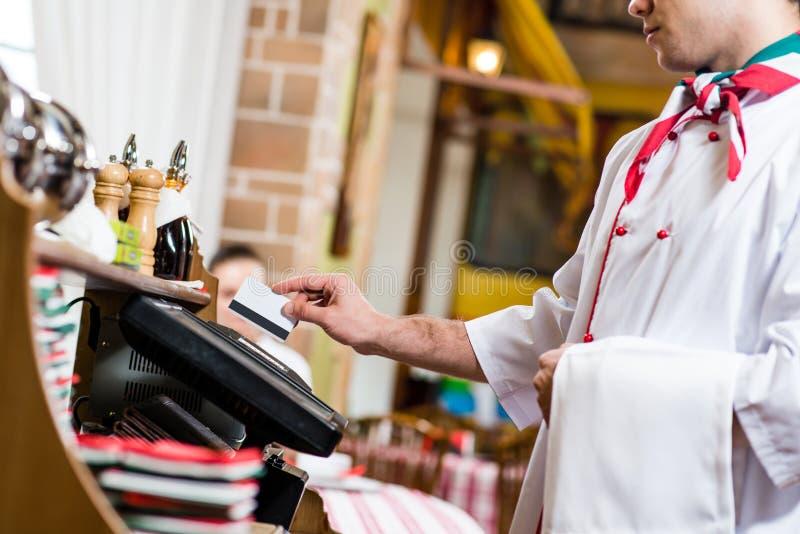 Kelner wkłada kartę w komputerowego terminal obraz stock