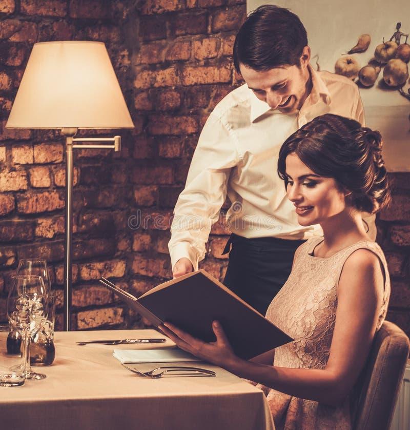 Kelner wyjaśnia menu piękna kobieta zdjęcia stock
