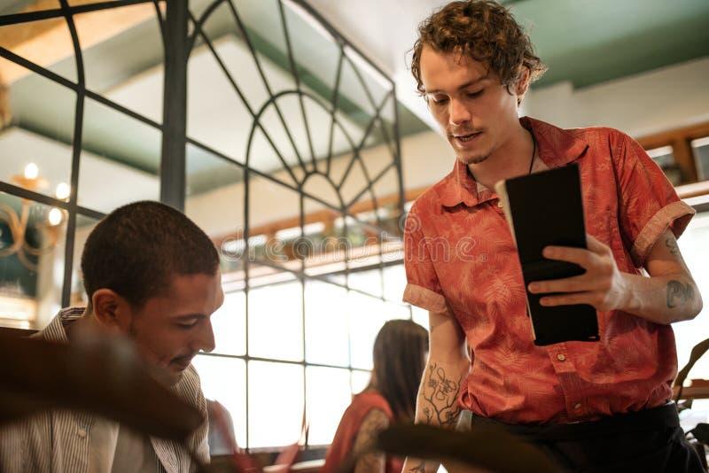 Kelner wyjaśnia menu uśmiechnięty restauracyjny klient obrazy royalty free