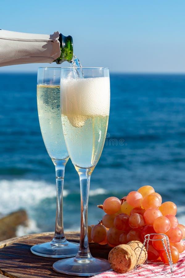 Kelnera dolewania szampan, prosecco lub cava w dwa szkłach na outside tarasie z dennym widokiem, zdjęcia royalty free