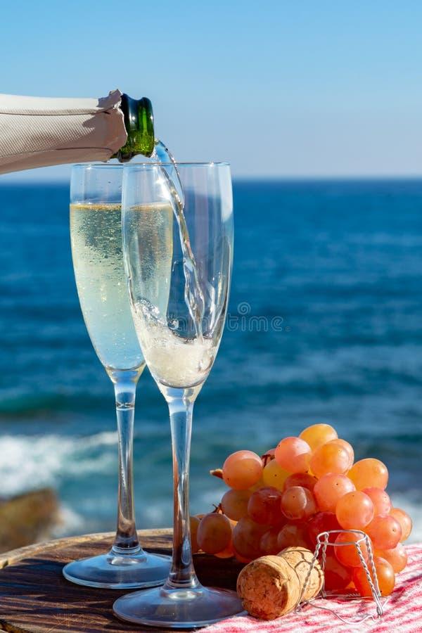 Kelnera dolewania szampan, prosecco lub cava w dwa szkłach na outside tarasie z dennym widokiem, zdjęcie royalty free