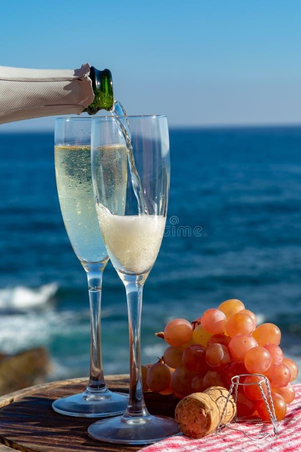 Kelnera dolewania szampan, prosecco lub cava w dwa szkłach na outside tarasie z dennym widokiem, zdjęcie stock