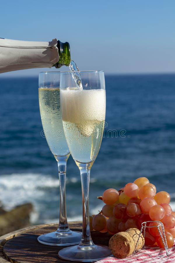 Kelnera dolewania szampan, prosecco lub cava w dwa szk?ach na outside tarasie z dennym widokiem, fotografia royalty free