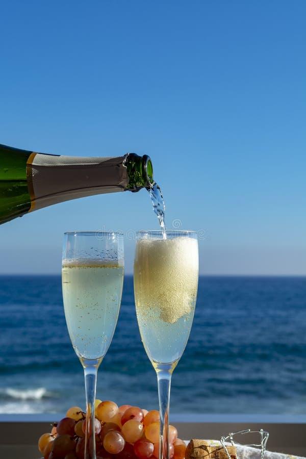 Kelnera dolewania szampan, prosecco lub cava w dwa szk?ach na outside tarasie z dennym widokiem, obrazy stock