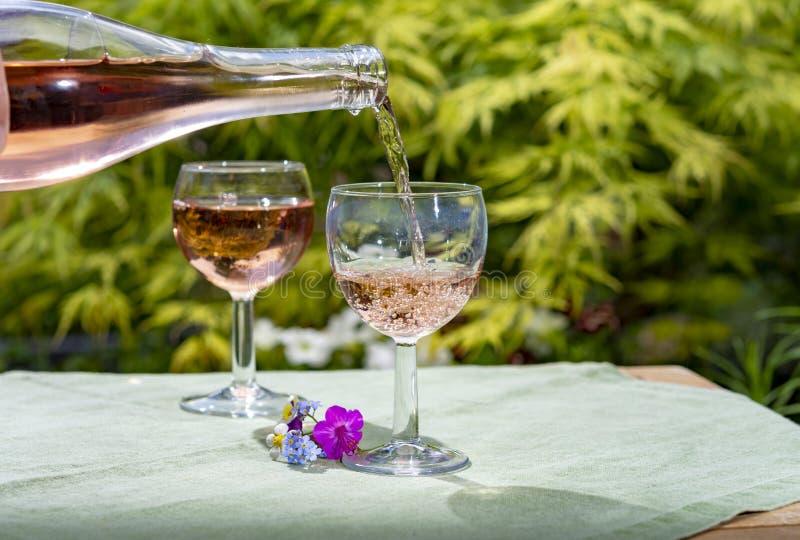 Kelnera dolewania zimna r??any wino w szk?ach w lato s?onecznym dniu w kwitn?? ogr?d zdjęcia stock