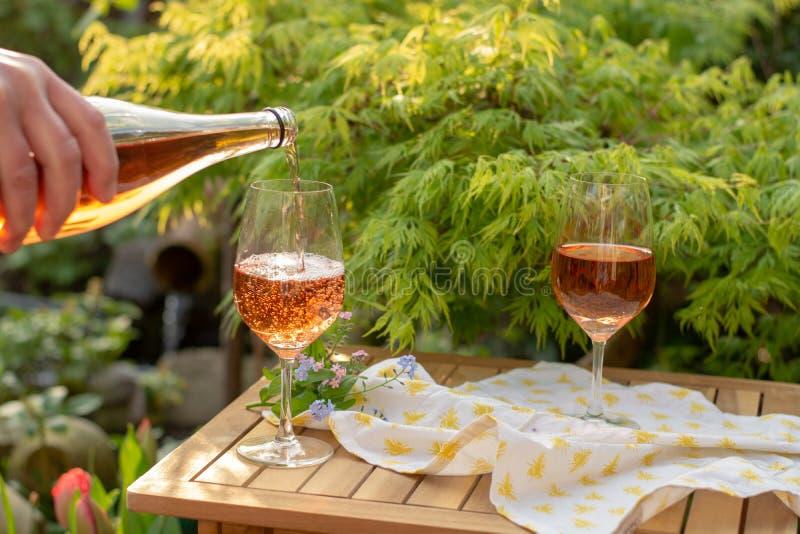 Kelnera dolewania zimno różany wino w szkłach na plenerowym tarasie w g fotografia stock