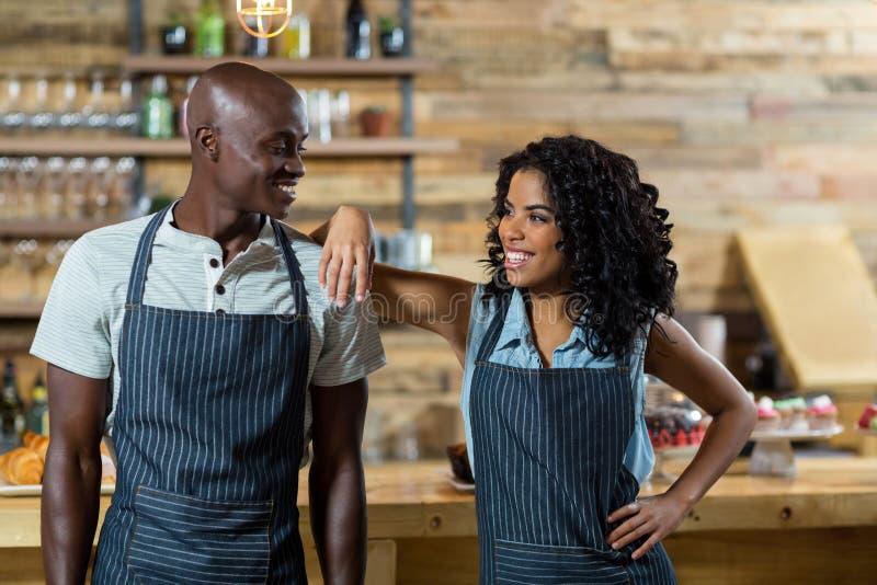 Kelnera i kelnerki pozycja przeciw kontuarowi w café zdjęcia royalty free