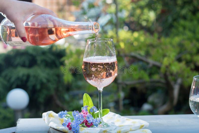 Kelnera nalewać glas zimna różany wino, plenerowy terrase, pogodny fotografia stock