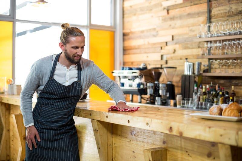 Kelnera obcieranie odpierający z pieluchą w café obraz royalty free