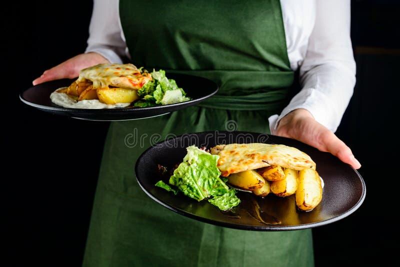 Kelnera przewożenia naczynia z grulami i mięsem zdjęcia stock
