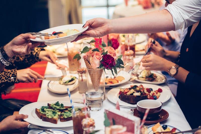 Kelnera serw klienci zgłaszają talerza z owocową sałatką na Niedziela rodziny śniadanio-lunch i dają zdjęcia stock