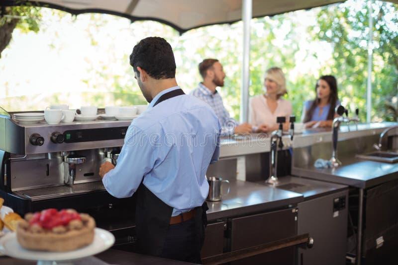 Kelnera używać majstruje naciskać zmieloną kawę w portafilter obraz stock