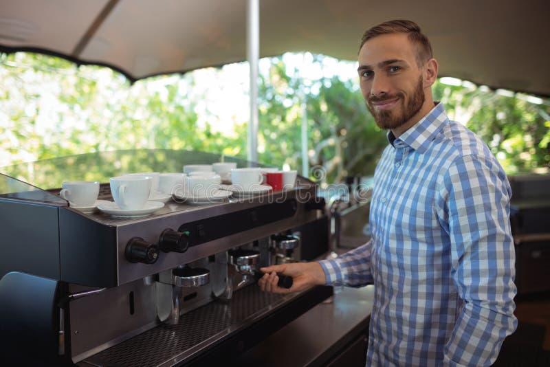 Kelnera używać majstruje naciskać zmieloną kawę w portafilter obrazy stock