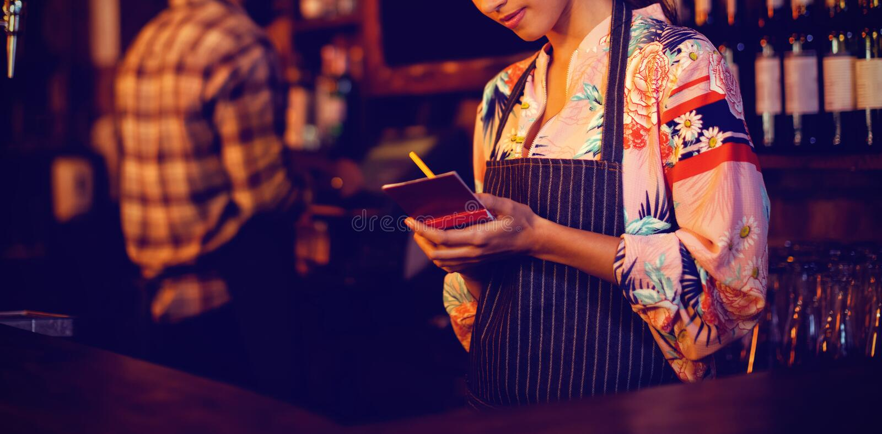 Kelnerka bierze rozkaz na notepad przy kontuarem obraz stock