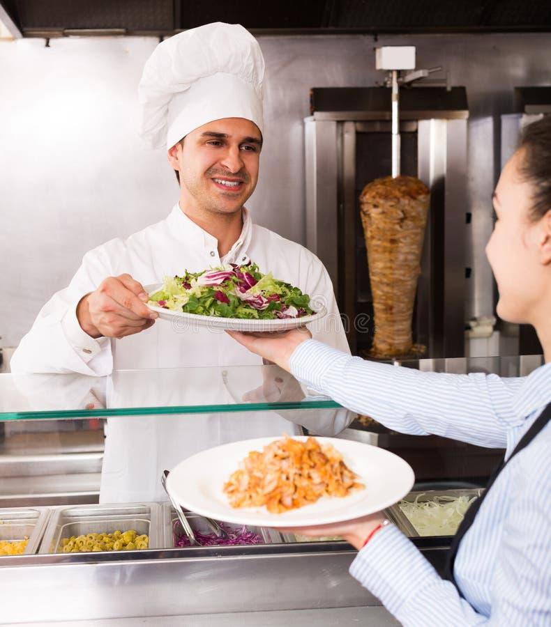 Kelnerka odbiorczy rozkaz z kebabem od szefa kuchni zdjęcie stock