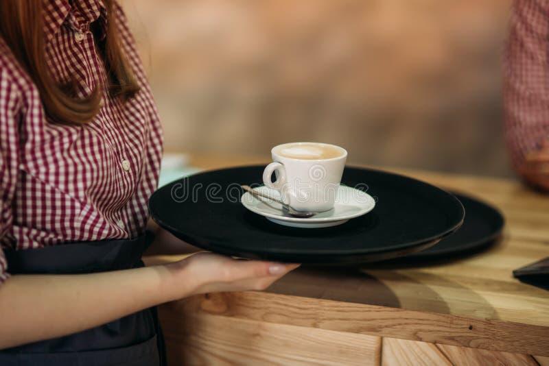 Kelnerka oferuje filiżankę kawy w kawiarni obrazy stock
