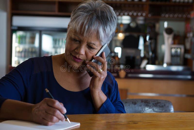 Kelnerka opowiada na jego telefonie obrazy royalty free