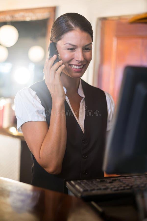 Kelnerka opowiada na telefonie przy kontuarem obrazy stock
