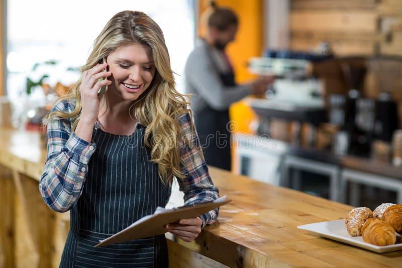 Kelnerka patrzeje schowek podczas gdy opowiadający na telefonie komórkowym w café fotografia stock