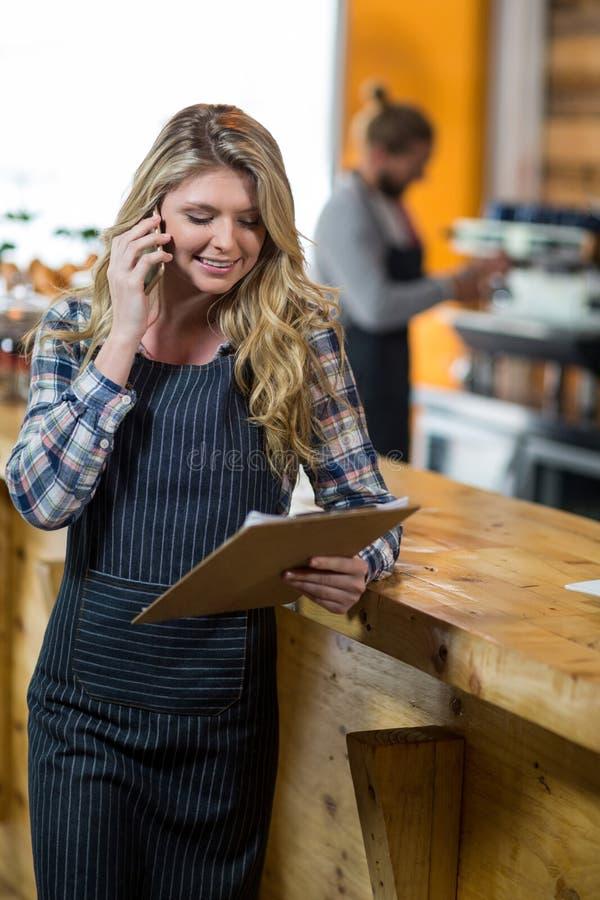 Kelnerka patrzeje schowek podczas gdy opowiadający na telefonie komórkowym w café zdjęcie stock