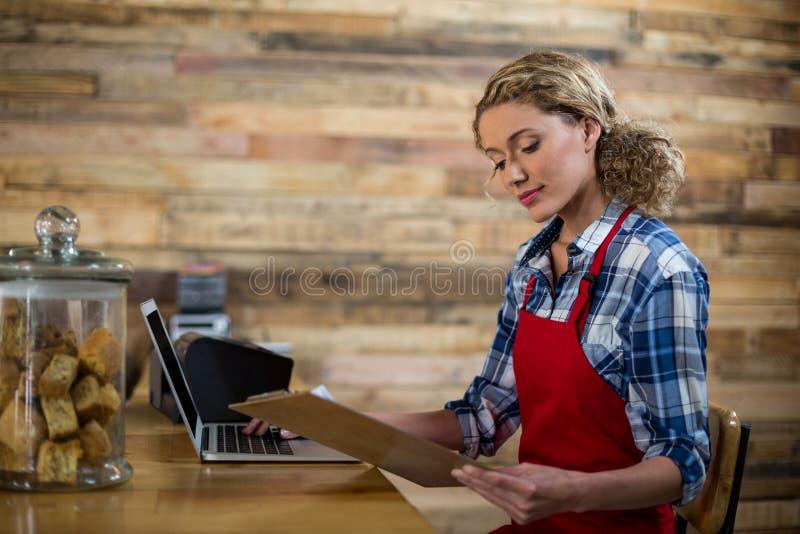 Kelnerka patrzeje schowek podczas gdy używać laptop w café zdjęcie stock
