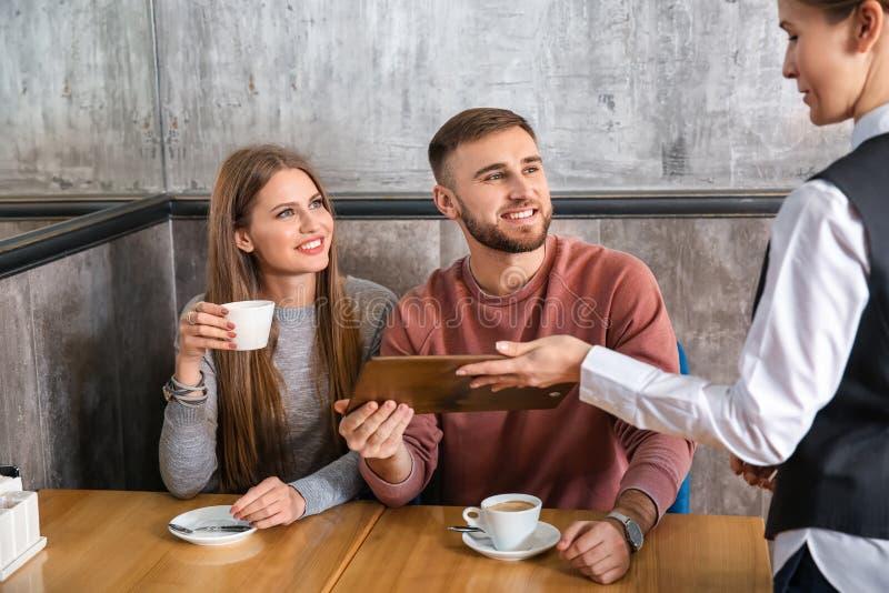 Kelnerka pokazuje potomstwa dobiera się menu w restauracji obraz stock