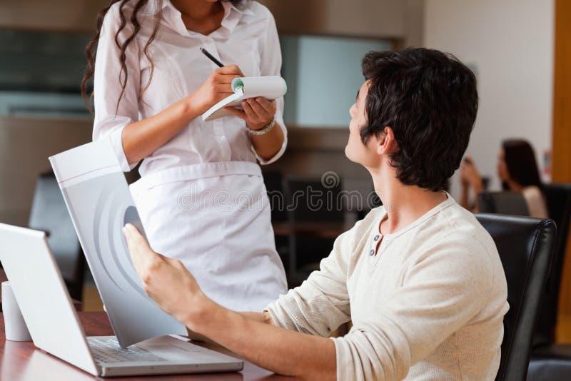 Kelnerka rozkazywać młodego człowieka jedzenie zdjęcia royalty free