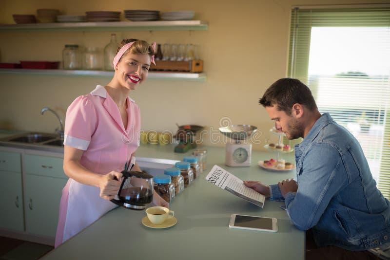 Kelnerka słuzyć czarną kawę podczas gdy mężczyzna czytelnicza gazeta zdjęcia stock