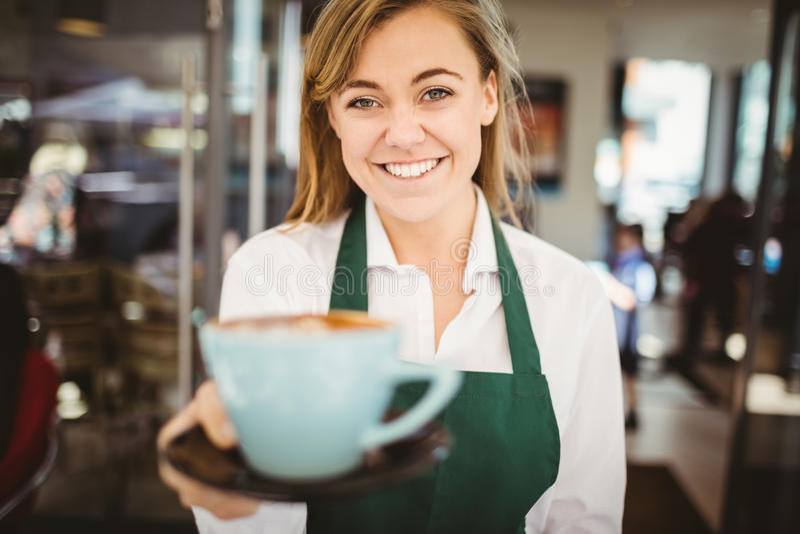 Kelnerka słuzyć filiżankę kawy obraz royalty free