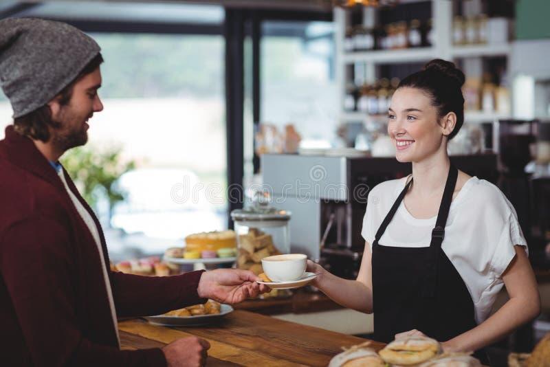 Kelnerka słuzyć filiżankę kawy klient obraz royalty free