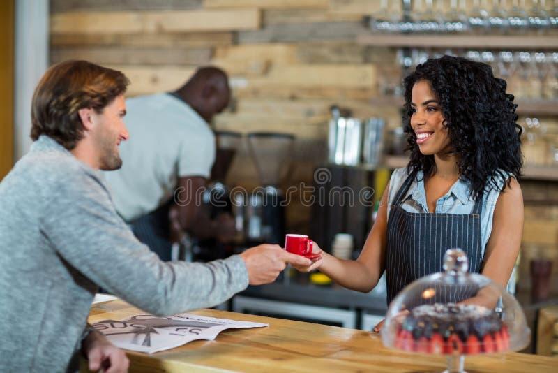 Kelnerka słuzyć filiżankę kawy przy kontuarem obrazy stock