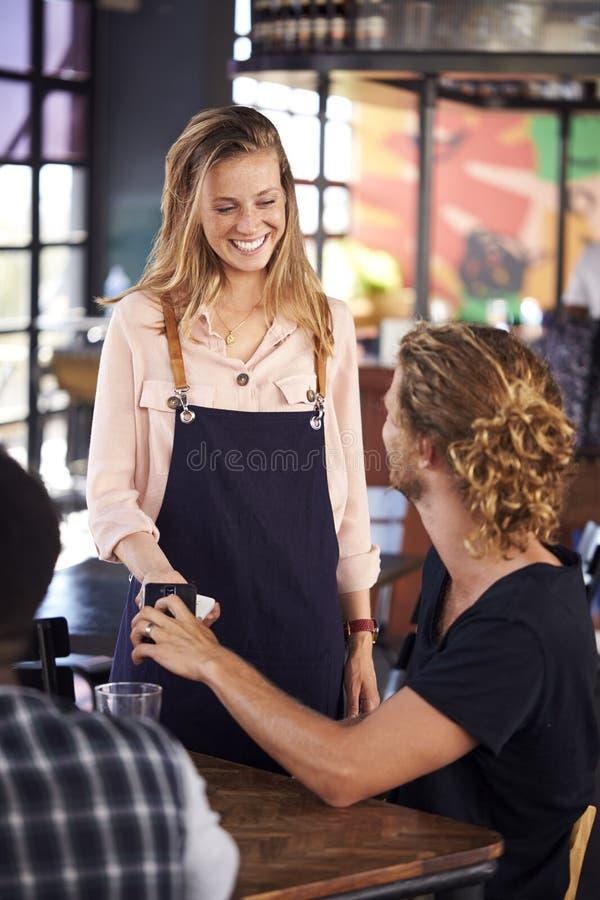 Kelnerka Trzyma Karcianą maszynę Gdy klient Robi Contactless zapłacie Dla Bill Używa telefon komórkowego fotografia stock