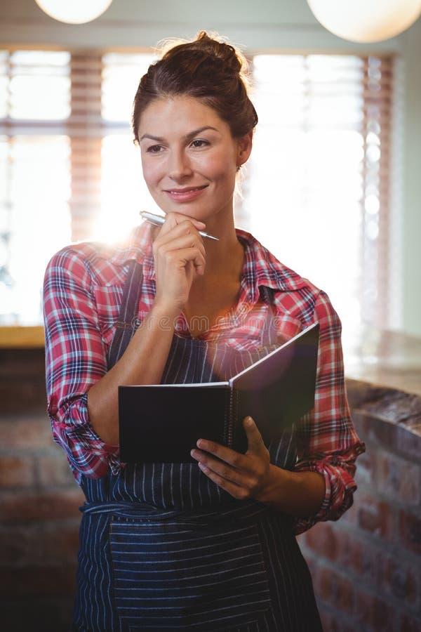 Kelnerka trzyma pióro i książkę zdjęcia royalty free