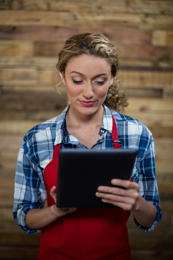 Kelnerka używa cyfrową pastylkę przeciw drewnianej ścianie obraz stock