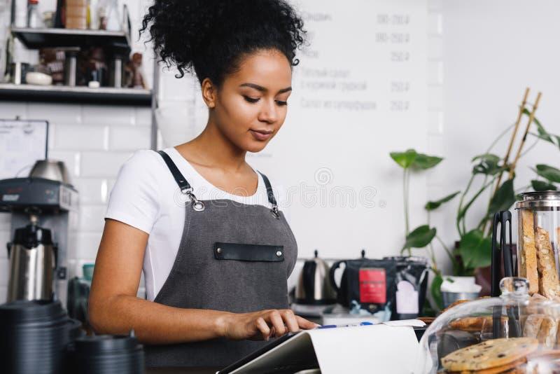 Kelnerka używa cyfrową pastylkę przy stołem obrazy stock