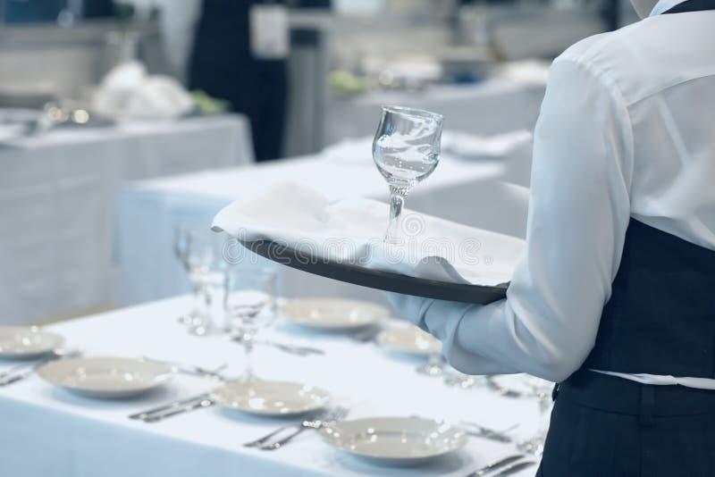 Kelnerka ubierał w jednolitej porcji set szkła obraz stock