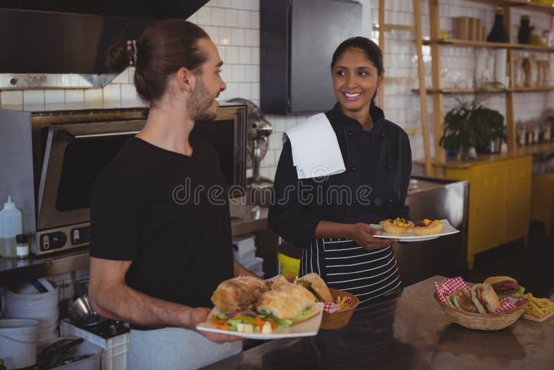 Kelnerka z karmowym patrzeje coworker w kawiarni obrazy royalty free