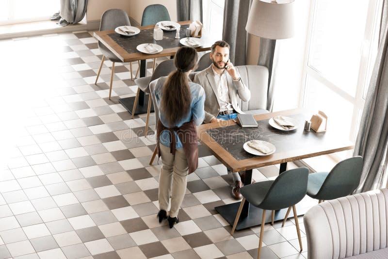 Kelnerki czekanie podczas gdy klient opowiada na telefonie fotografia stock