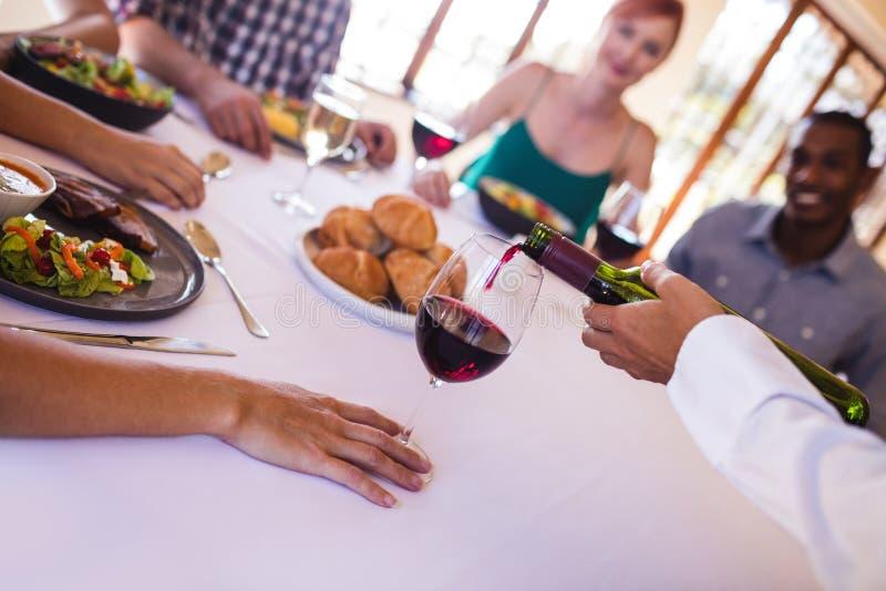 Kelnerki dolewania czerwone wino w wina szkle na stole obraz stock