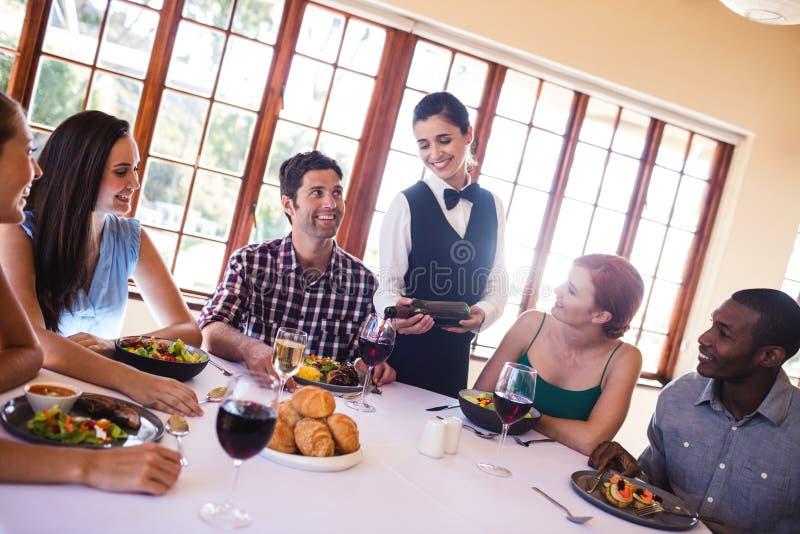 Kelnerki dolewania czerwone wino w wina szkle na stole fotografia royalty free