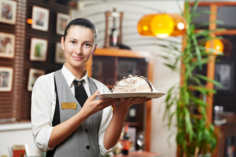 Kelnerki dziewczyna z tortem na talerzu przy restauracją obraz royalty free