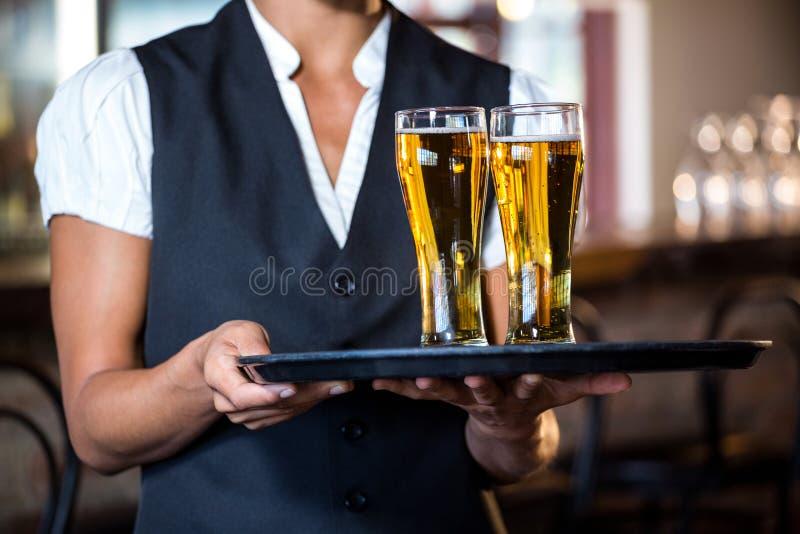Kelnerki mienia porci taca z dwa szkłami piwo obrazy royalty free