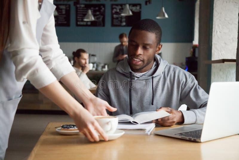 Kelnerki porci kawa uśmiechnięty afroamerykański mężczyzna klient zdjęcie stock
