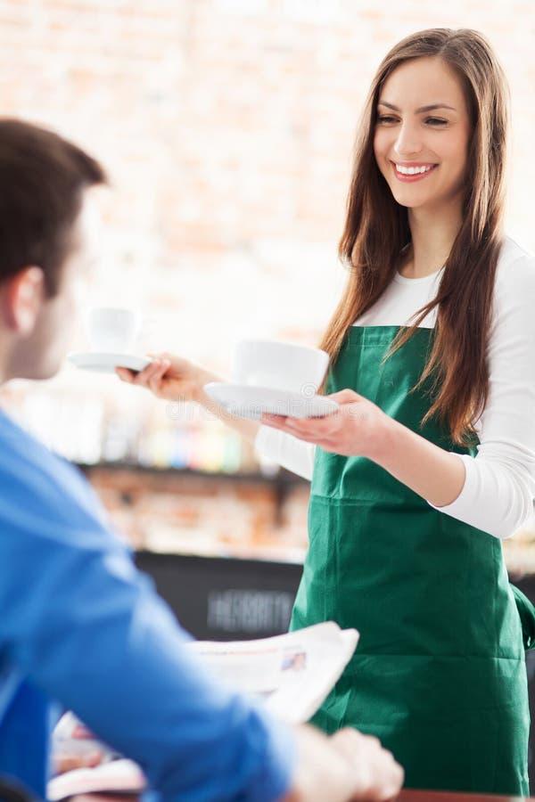 Kelnerki porci mężczyzna przy kawiarnią zdjęcia royalty free