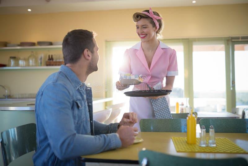 Kelnerki porci posiłek obsługiwać w restauraci fotografia royalty free
