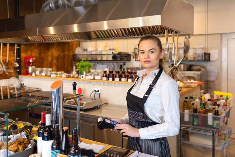 Kelnerki pozycja przy gotówkowym kontuarem trzyma elektronicznej karty płatniczą maszynę - Uśmiechniętego młodej kobiety mienia b zdjęcia royalty free