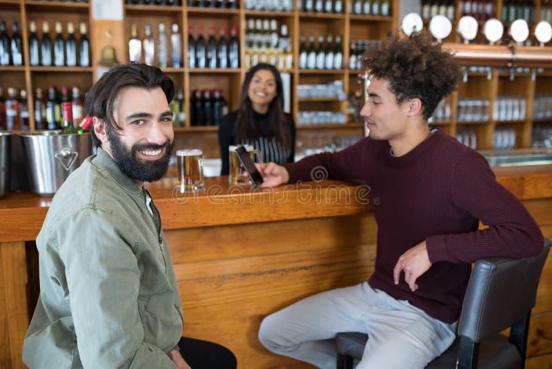 Kelnerki pozycja przy kontuarem podczas gdy dwa mężczyzna używa telefon komórkowego obraz royalty free