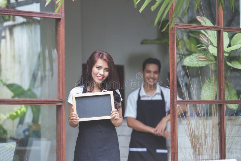 Kelnerki pozycja przy przodem cukierniani zapraszający ludzie przychodzić zdjęcia royalty free