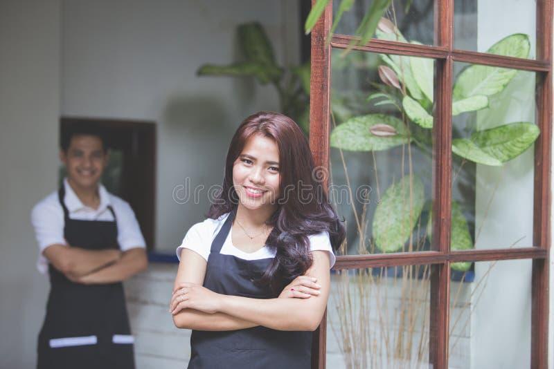 Kelnerki pozycja z rękami krzyżować w kawiarni obraz royalty free